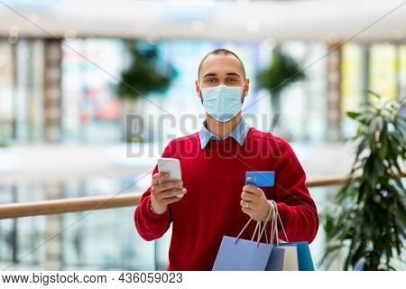 Young Caucasian Guy Holding Shopper Bags, Using Smartphone And Credit Card, Paying For Purchase Onli