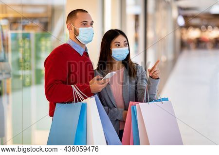 Young Multiracial Couple Wearing Face Masks, Walking With Shopper Bags At Mall, Checking Shopping Li