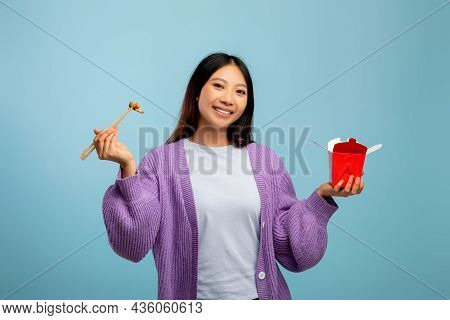 Food Delivery, Fastfood Concept. Asian Lady Eating Noodles With Chopsticks, Holding Paper Box Over B