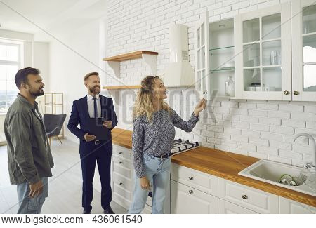 Couple Planning To Buy New Home, Meeting With Realtor And Looking Around The House