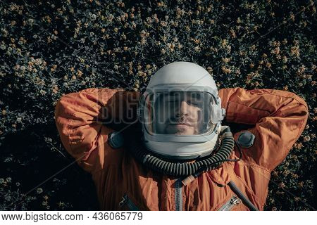 Closeup Of Cosmonaut Wearing Space Suit And Space Helmet Taking A Nap While Lying On Grass Outdoors.