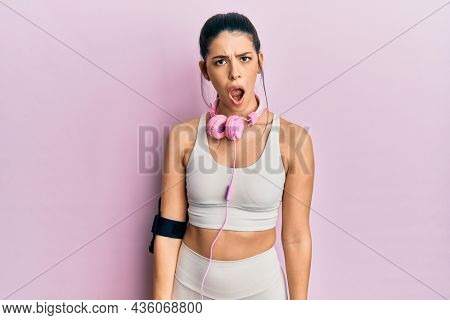 Young hispanic woman wearing gym clothes and using headphones in shock face, looking skeptical and sarcastic, surprised with open mouth