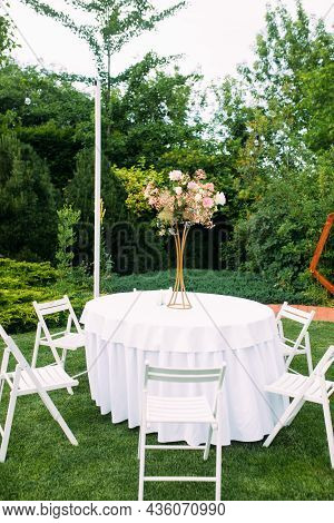 Table Covered White Tablecloth With Bouquet And Chairs Around It Are On At Wedding Banquet In Lawn A