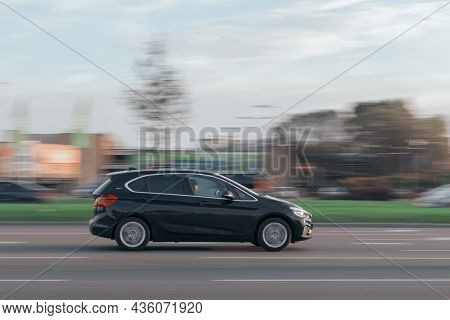 The Bmw 2 Series Is Driving At High Speed On The Street. The Car Has A Hybrid Engine. Motion Blur. R