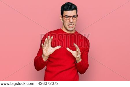 Handsome hispanic man wearing casual clothes and glasses disgusted expression, displeased and fearful doing disgust face because aversion reaction. with hands raised