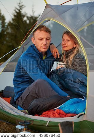 Family Couple Of Mountain Campers Resting On Glade In Tent. Husband, Lowering His Eyes, Thinking Abo