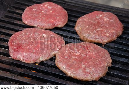 Raw Meatballs For Burgers Are Fried On Grill. Meat Is Roasting On Bbq Grill Outdoor.