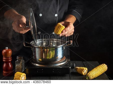 Professional Cook Cooks Corn. Close-up Of A Chef Is A Hand While Cooking In A Restaurant Kitchen. Fr