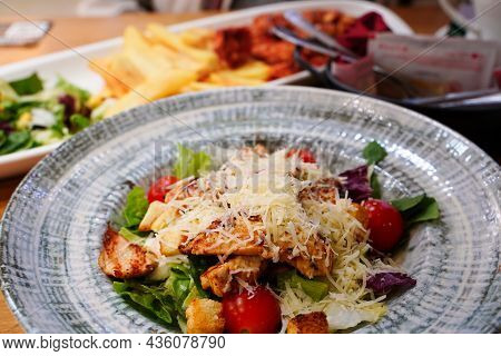 Caesar Salad With Chicken And Cheese In A Round Gray Plate. Shallow Depth Of Field