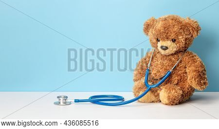 Teddy Bear And Stethoscope On A Blue Background. Pediatrician Concept. Template Copy Space For Text