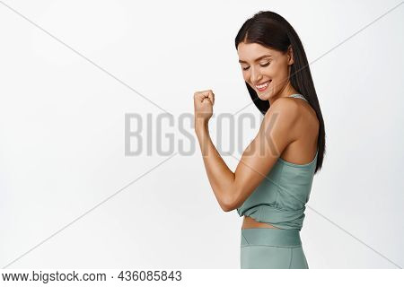 Smiling Sportswoman Flexing Biceps, Looking Pleased At Her Arm. Concept Of Female Athletes And Worko