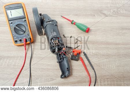Power Tool Repair. Angle Grinder Disassembled For Repair On A Wooden Table In A Repair Shop. Multime