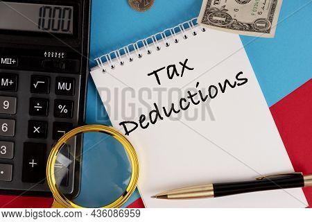 Tax Deductions, The Text Is Written In A White Notepad, Next To A Calculator, A Pen And A Magnifying