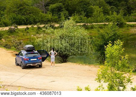 A Blue Car With A Girl With A Black Roof Rack Stands Against The Background Of A Mountain Lake With