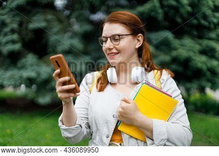 Happy Beautiful Female Student Teenager In Eyesight Glasses Using Smart Mobile Phone. Female Holds B