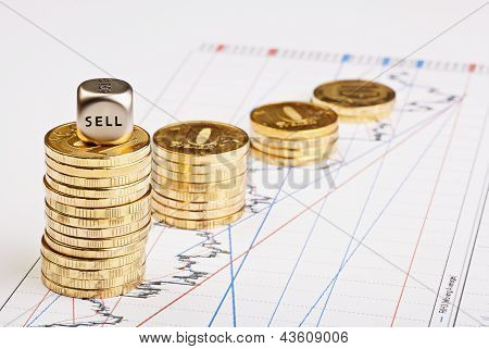 Coins Stacks Downtrend And The Dices Cube With The Word Sell On Financial Chart. Selective Focus