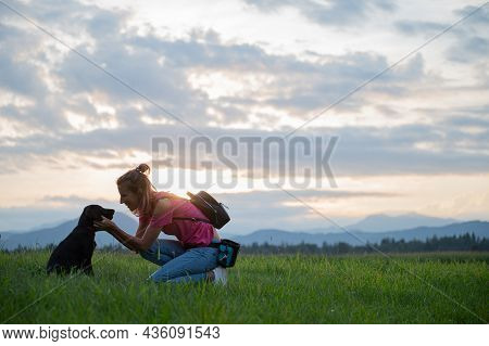 Happy Cheerful Young Woman Kneeling Down To Cuddle Her Cute Black Labrador Puppy As They Are Outside