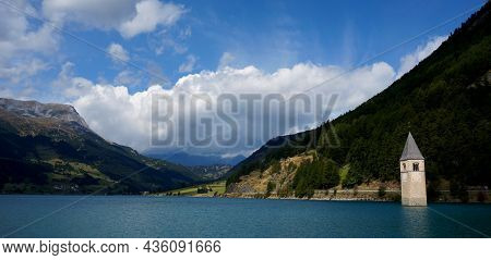 Wonderful Panoramic View Of The Lake Resia. Famous Tower In The Water. View From Graveyard To Church