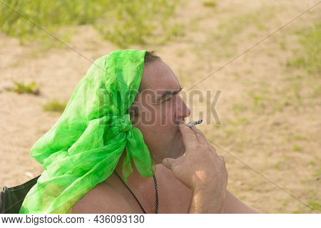 Portrait Of Man In Profile With Scarf On His Head. Pensive Man Smokes A Cigarette.