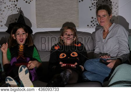 Mother With Her Daughters Watching A Horror Movie On Halloween