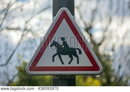 Rider On Horse Is A Road Sign Warning Of  Possible Meeting. Triangular Sign With Red Stripe And Dark