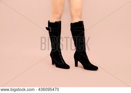 Beautiful Caucasian Sexy Woman Legs In Black Suede Slim High Stiletto Heels Boots On Light Pink Back