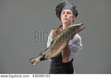 A male chef cook in a cook's uniform holds fresh salmon on a gray background. Food and meals. Studio portrait.