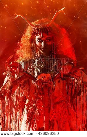 Portrait of a frightening shaman woman with a staff in her hands doing her sinister ritual among mysterious red light and haze. Ethnic traditions. Paganism. Halloween.