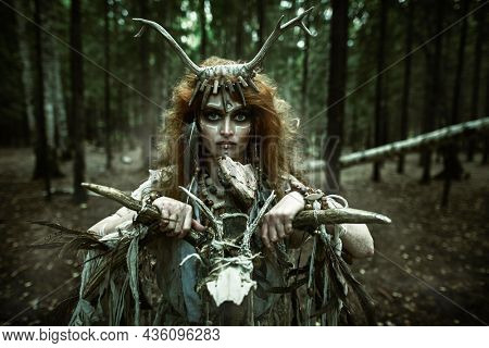 Portrait of a female shaman in an ethnic dress and deer antlers headdress holding a ritual staff standing in a gloomy dense forest. Fantasy concept, magic. Paganism. Halloween.