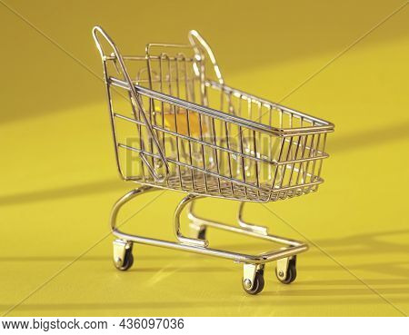 Shopping Cart On Yellow Background With Daylight. Supermarket Trolley.