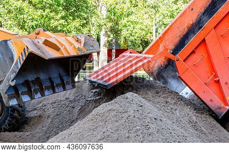 Front Loader And Dump Truck Unload Sand At A Construction Site