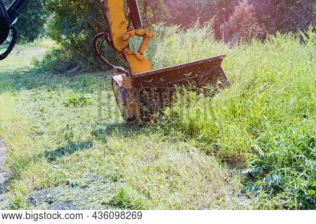 Road Services Are Engaged In Tractor With A Mechanical Mower Mowing Grass On The Side Of The Asphalt