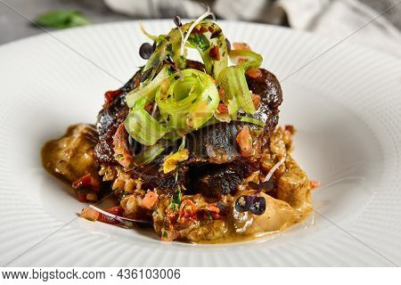 Braised beef cheeks with pearl barley and celery in creamy mushroom sauce. Veal cheek with mushroom risotto on gray stone background. Main course concept. Food menu for restaurant
