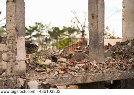 The Remains Of The Destroyed Building: Load-bearing Columns, A Concrete Floor And A Pile Of Broken B