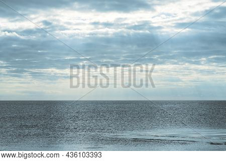 Natural Background Of Cloudy Sky Over The Sea In The Morning Twilight. The First Rays Of The Sun Are