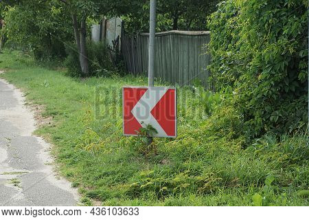 One Road Sign Turning Direction With Red Arrows In The Green Grass By The Asphalt Road