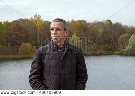 Adult Retired Man Stands By The Lake On Beautiful Autumn Day And Is Resting. Slowdown Concept. Selec