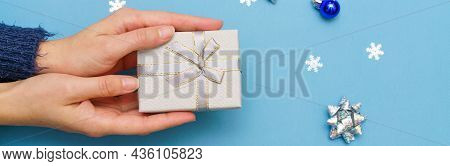 Womans Hands Holding Gift Box Present, Tied With Ribbon Bow On Blue Background Around Christmas Tree