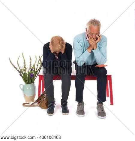 Sadness senior couple in waiting room isolated over white background