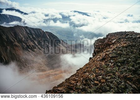 View From Precipice Edge With Sharp Rocks And Snow Cornice Above Clouds To Mountain Valley In Low Cl