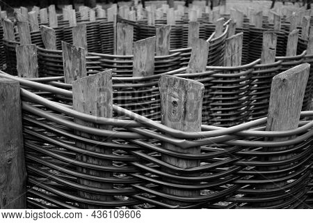 Selective Focus On Wooden Fence Posts Of Intertwined Plastic Pipes. Polypropylene Plumbing Pipes In