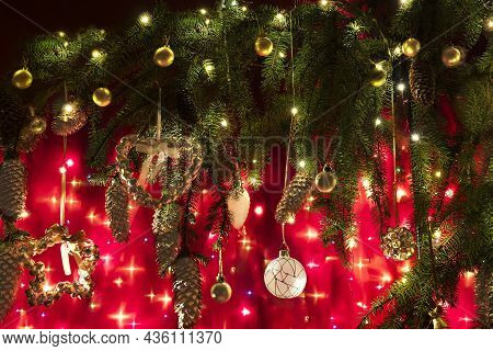 Greeting Card With A Branch Of A Christmas Tree With Christmas Decorations And Garlands. Dark Festiv