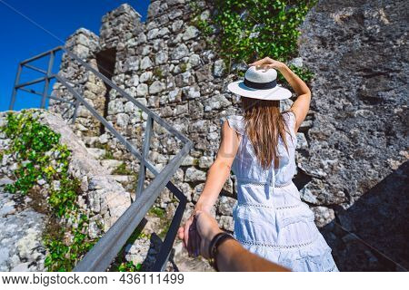 Carefree Tourist Woman In White Dress And Sun Hat Leading Her Boyfriend. Follow Me. Couple On Vacati
