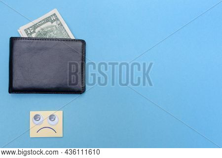 Two Dollars Are In The Wallet. Place For Your Text. Copy Space. Sad Smiley Looks At The Wallet. Blue
