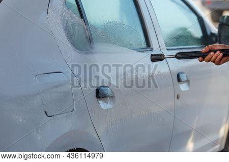 Hand With High Pressure Washer Washing White Car At Public Self-service Car Washing Station, Close-u