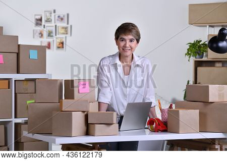 Middle Aged Asian Woman Entrepreneur, Business Owner Working On Laptop Computer Checking Address And