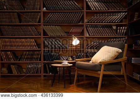 Cozy Home Library Interior With Comfortable Armchair And Collection Of Vintage Books On Shelves