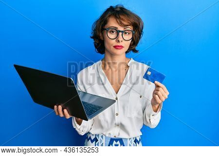Young brunette woman wearing business style holding laptop and credit card relaxed with serious expression on face. simple and natural looking at the camera.