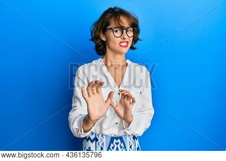 Young brunette woman wearing casual clothes and glasses disgusted expression, displeased and fearful doing disgust face because aversion reaction. with hands raised