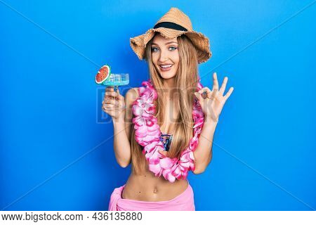Young blonde girl wearing bikini and hawaiian lei drinking cocktail doing ok sign with fingers, smiling friendly gesturing excellent symbol